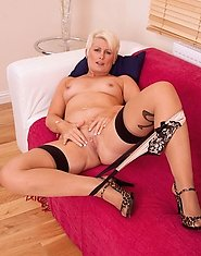 Seductive hot milf Sally Taylor satisfies her pussy with a silver dildo on the couch